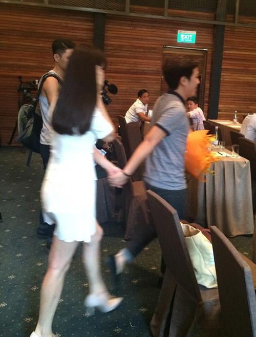 """Trường GIang nắm tay Nhã Phương dẫn vào bên trong khi cô bất ngờ xuất hiện tại buổi họp báo liveshow """"Chàng hề xứ Quảng""""."""