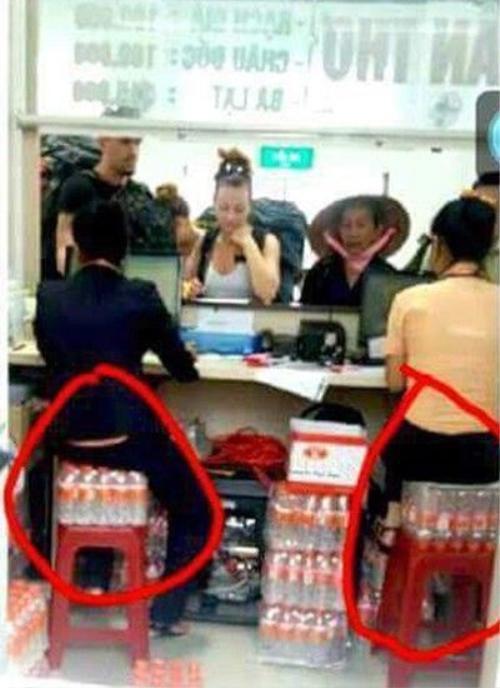 Trước mặt hai nhân viên ngồi trên nước uống cho khách là những hành khách nước ngoài.