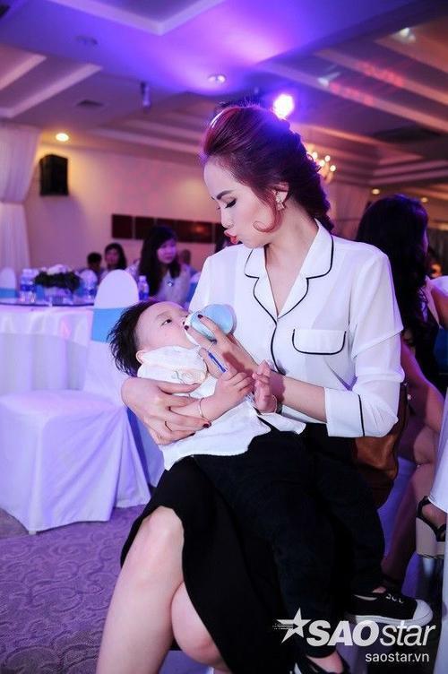 """Cô tranh thủ cho bé Noah Nguyễn """"nạp năng nượng"""" trước khi sự kiện bắt đầu."""