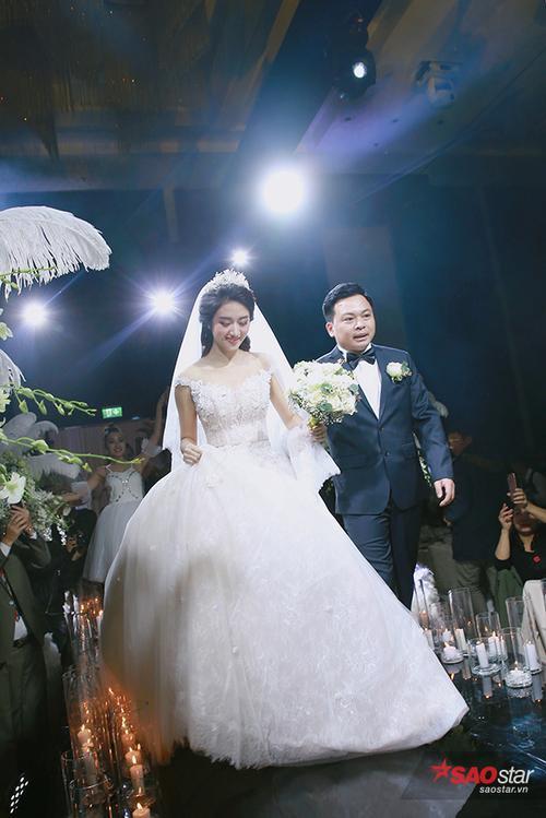 Cô dâu chú rể năm chặt tay tiến vào khán phòng làm lễ.