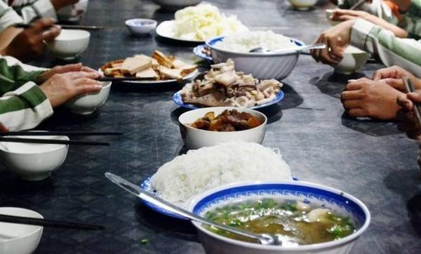 Trên bàn ăn gồm các món rau xanh, thịt kho, chân giò hầm, chả lụa...