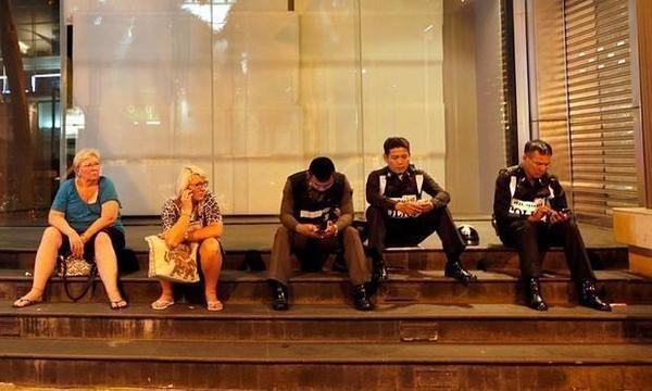 Khách du lịch ngồi cạnh cảnh sát Thái Lan trước cửa một trung tâm mua sắm gần hiện trường vụ nổ. Ảnh: Guardian