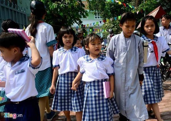 Kết thúc lễ khai giảng, Huyền cùng các bạn bước ra. Trên tay bé là món quà của nhà trường tặng.