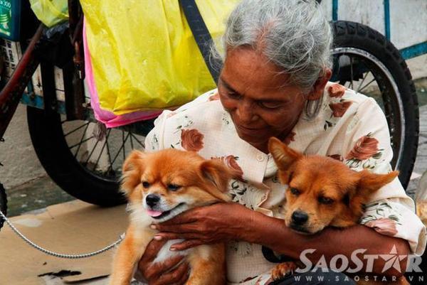 """""""Nhà"""" bà là  tấm bạt cũ che tạm trên chiếc ghế bố ở vỉa hè đường Nguyễn Thông (quận 3). Hơn 2 năm qua bà làm nghề nhặt ve chai, sống cùng bà còn có 2 chú chó nhỏ, vì yêu quý chúng bà đặt tên là Ti (con cái) và Na (con đực)."""
