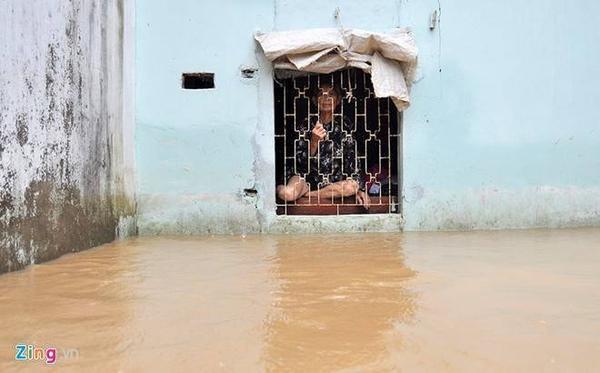 Cụ Phạm Thị Hiến (90 tuổi) nhìn khoảng sân bị nước lũ nhấn chìm. Ảnh: Ngọc An.