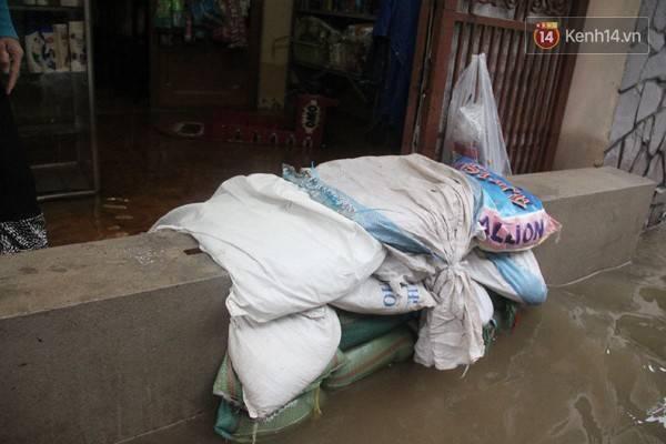 """Mặc dù xây thêm tường, và """"đắp đê"""" ngăn nước ngập, nhưng nhà chị Thanh vẫn đang vất vả chóng chọi với nước."""