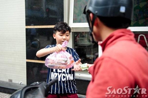 Cậu nhóc vui vẻ bán bánh cho khách trong khi mẹ mình tất bật chiết nước chấm vào túi ni lông nhằm kịp giờ giao số hàng đặt.