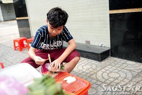 Thí sinh 12 tuổi gốc Phan Thiết giúp mẹ chất hàng ra bàn nhựa và tự tay bỏ từng chiếc chả vào các hộp bánh đang làm dang dở.