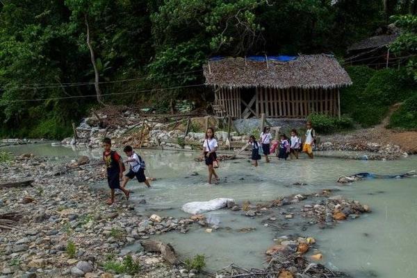 Các em nhỏ lội qua dòng sông trắng xóa do thủy ngân tan vào trong nước.