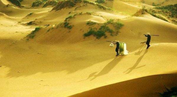 Ngư dân đi biển về qua đồi cát ở Bãi Môn.