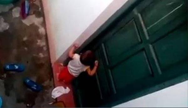 Cháu bé khóc lóc đập cửa nhưng không ai để ý. Ảnh cắt từ clip