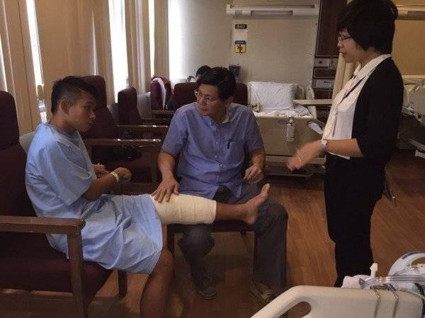 Anh Khoa (bìa trái) trò chuyện với bác sĩ Tan Jee Lim sau khi mổ. Ảnh do bệnh viện Parkway cung cấp.