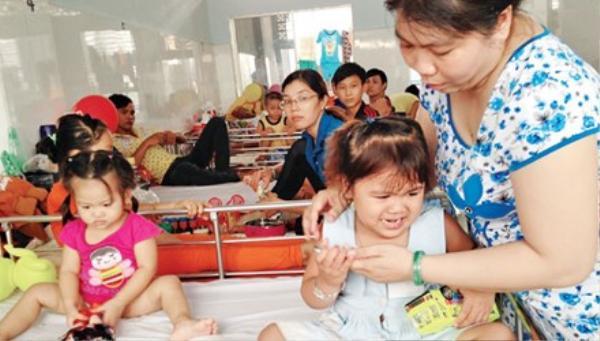 Hai bệnh nhi chia nhau 1 giường bệnh tại khoa sốt xuất huyết Bệnh viện Nhi đồng 1 TPHCM. Ảnh: Quốc Ngọc.