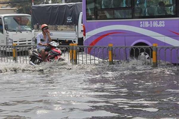 Mực nước trên đường Kinh Dương Vương lên đến nửa bánh xe - Ảnh: Phạm Hữu