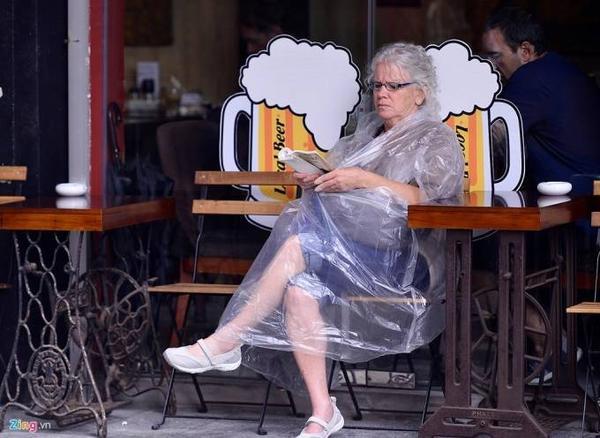 Một du khách quốc tế mặc áo mưa uống cà phê trên phố Nguyễn Hữu Huân.