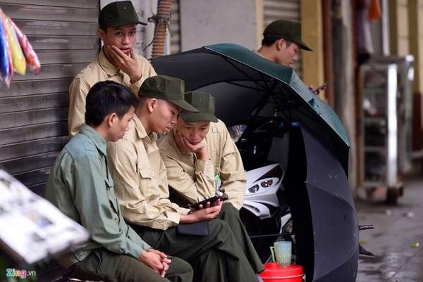 Một nhóm bảo vệ trên phố Tràng Thi phải dùng ô che chắn gió.