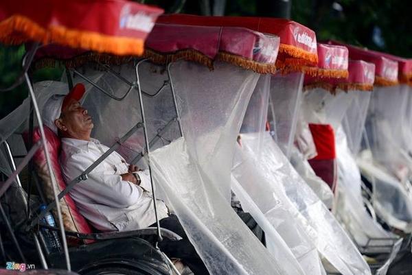Đội xích lô dùng áo mưa che chắn để chống gió. Có người còn khoanh tay ngủ luôn trên xe.