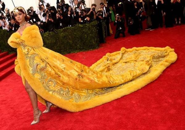 Và bộ đồ gây sốt nhất thời gian vừa qua là đây. Có mặt trên thảm đỏ chương trình Met Gala 2015, Rihanna khiến tất cả mọi người phải xuýt xoa, choáng váng với diện mạo sang trọng của nữ ca sĩ trong chiếc áo cape lông vàng rực, nặng tới 25 kg, phần đuôi dài lê thê được in các họa