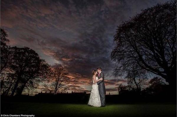 Chú rể và cô dâu nhìn nhau đắm đuối dưới khung cảnh nền tối bầu trời nhiều mây tuyệt đẹp.