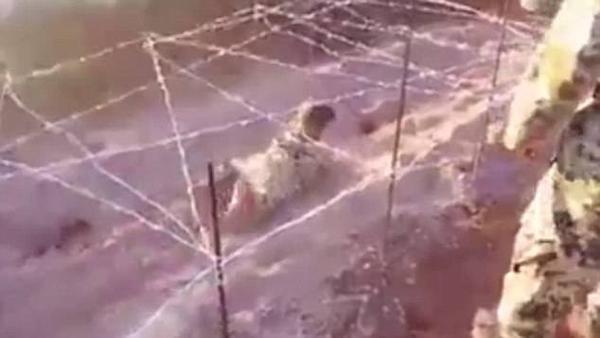 Cậu bé đang trườn dưới hàng rào dây kém sắc nhọn trong khi các chiến binh khủng bố bắn vài phát đạn ngay đầu và chân nhằm uy hiếp tinh thần.