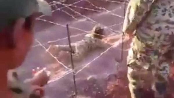 Bên cạnh là những tên lính khủng bố đứng giám sát đứa bé vừa khóc lóc hoảng loạn vừa cố trườn bò tránh đạn.