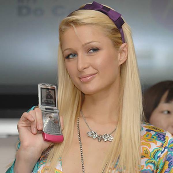 """Từng là nàng tiểu thư ăn chơi """"nức tiếng"""" của tập đoàn khách sạn Hilton, cô nàng Paris Hilton đương nhiên không thể bỏ qua những mẫu điện thoại thời thượng nhất theo từng thời kỳ. Báo chí từng bắt gặp cô với chiếc điện thoại nắp gập Motorola RAZR màu hồng trên tay tại một buổi tiệc."""