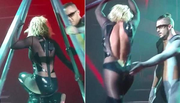 """Hôm 17/10, Britney Spears tiếp tục chuỗi show diễn Piece Of Me ở Las Vegas. Khi đang biểu diễn, nữ ca sĩ gặp sự cố với bộ jumpsuit. Trong lúc trình diễn, phần khóa phía sau lưng bất ngờ bị tuột dài đến tận hông Britney, nữ ca sĩ vẫn hát nhưng ra hiệu """"cầu cứu"""" các vũ công tới giúp. Mặc dù có 2 vũ công nam đến giúp nhưng chiếc khóa bị mắc kẹt, Britney đành bỏ mặc sự cố cho đến hết màn trình diễn."""