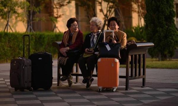 Một nhóm các cụ bà ngồi chờ ngoài khách sạn trước khi được đưa qua biên giới đến buổi gặp mặt. Sự kiện này do Hội chữ thập đỏ tổ chức với sự đồng ý và giám sát của chính phủ hai miền Triều Tiên hồi tháng 8 vừa qua.