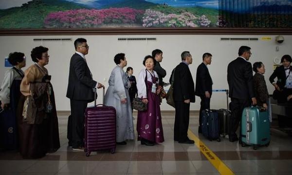 Những người Hàn Quốc xếp hàng đứng đợi kiểm tra an ninh ở biên giới.