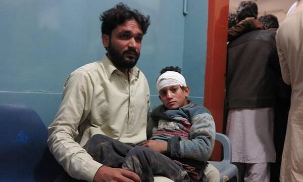 Một cậu bé bị thương vì đất đá rơi vào đầu đang được cha chăm sóc ở bệnh viện Mingora, Pakistan.