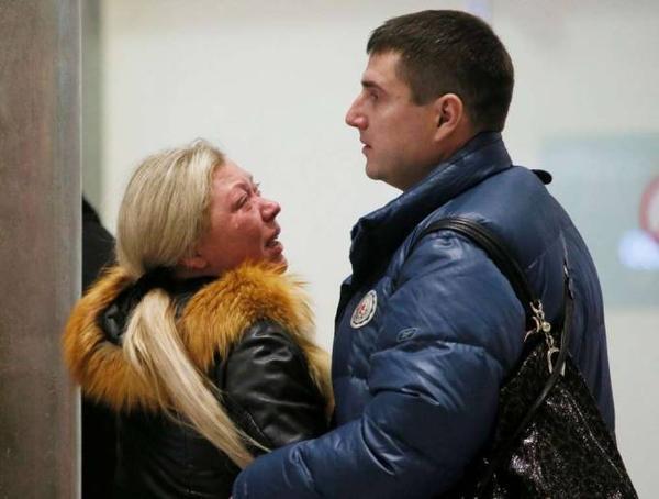 Một phụ nữ khi nghe tin dữ về thân nhân của mình khóc ngất trên vai chồng.