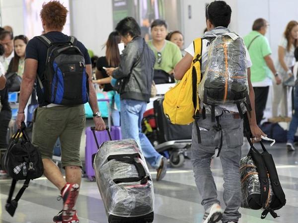 Nhiều hành khách tại sân bay Ninoy Aquino bao bọc kỹ hành lý để tránh bị gài đạn - Ảnh: Reuters