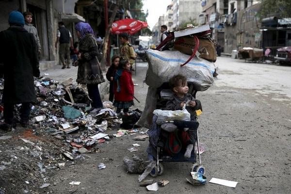Em bé ngồi trong xe đẩy chờ mẹ đi nhặt bìa cạc tông để đốt lửa sưởi ấm tại Douma hôm 17/11/2015.
