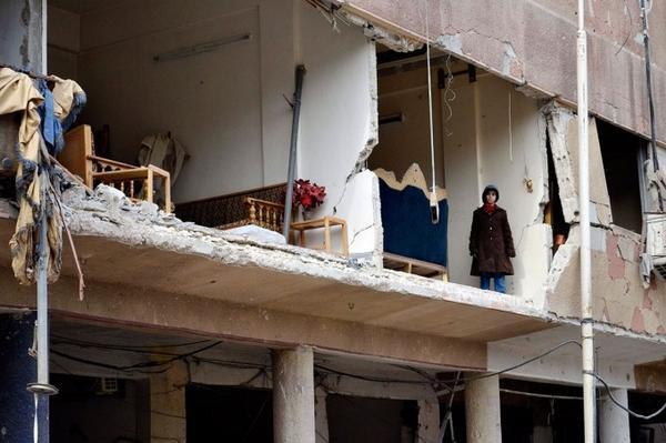 Một cô bé đứng ngay trên căn nhà bị đánh bom sau trận tấn công của quân đội Syria tại Douma hôm 6/2/2015.