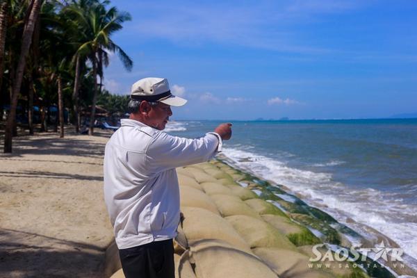 """Ông Nguyễn Xin, bảo vệ tại khu bờ biển Cửa Đại cho biết: """"Bờ biển hồi trước đẹp lắm, bây giờ sóng đánh bay mất 5 hàng dừa rồi, ăn sâu vào đất liền cả 50m rồi chứ chẳng chơi""""."""