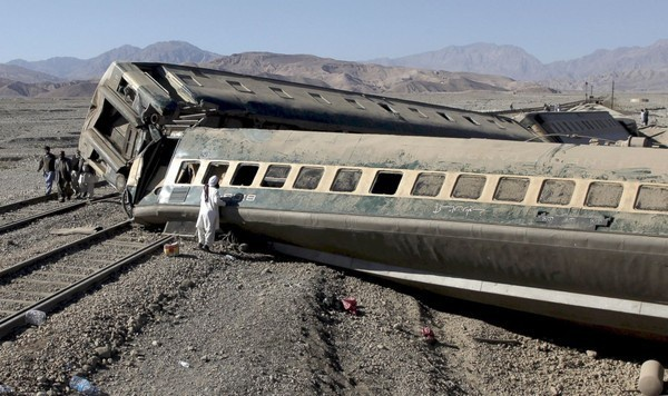Một hành khách đang cố tìm lại tài sản của mình trong toa tàu bị lật vì trật đường ray tại Quetta, Pakistan.