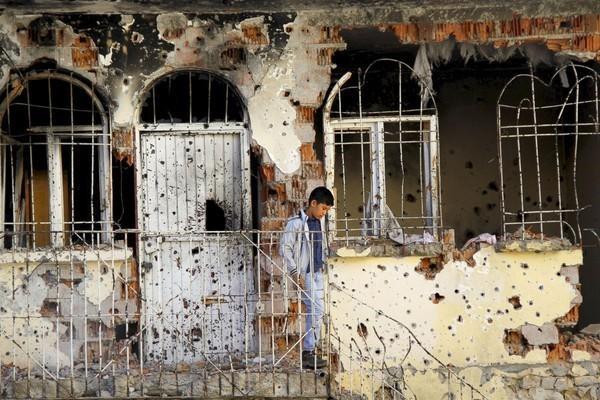 Cậu bé bên ngoài tòa nhà tan nát vì súng đạn trong cuộc xung đột giữa Lực lượn an ninh Thổ Nhĩ Kỳ và phiến quân người Kurd tại Silvan, Thổ Nhĩ Kỳ.