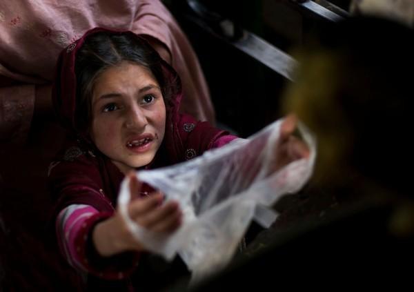Cô bé nghèo người Pakistan đang đi xin thức ăn từ thiện cho cả gia đình trong một buổi phát thức ăn được tổ chức tại ngôi đền địa phương phía ngoại ô thủ đô Islamabad.