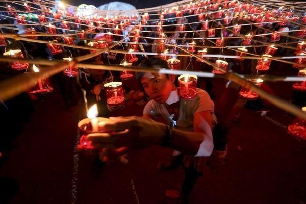 """Cảnh người dân thắp nến trước khi thả khinh khí cầu giấy trong lễ hội Tazaungdaing, hay còn gọi là """"Lễ hội dệt y cho Đức Phật"""". Đây là một trong những lễ hội ngoạn mục nhất được tổ chức vào tháng 11 hàng năm ở Taunggyi, miền nam bang Shan, Myanmar. Tazaungdaing bắt đầu từ kỳ trăng tròn tháng Tazaungmone và kéo dài trong 3 ngày."""