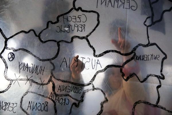 Những đứa trẻ tị nạn đang chỉ vào các quốc gia tiếp nhận di dân trên bản đồ tự chế bên trong một túp lều ở trại tị nạn gần Trung tâm đăng ký tị nạn trên đảo Lesbos, Hi Lạp. Sau vụ việc ngày 13/11, rất nhiều nơi trên thế giới đã bắt đầu tẩy chay người tị nạn Syria và thắt chặt công đoạn xét duyệt hồ sơ gắt gao hơn rất nhiều.