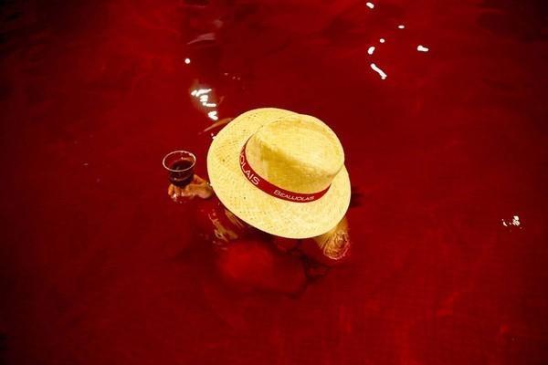 Người phụ nữ ngâm mình trong bể nước màu rượu và thưởng thức ly rượu vang tại khu nghỉ dưỡng Kowakien Yunessun, tỉnh Hakone. Đây cũng là hoạt động kỷ niệm Ngày lễ rượu vang Beaujolais Nouveau truyền thống của Pháp, diễn ra thường niên vào nửa đêm thứ 5 thứ 3 trong tháng 11.