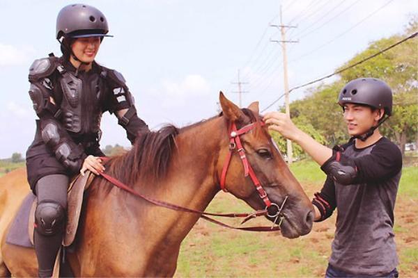 """Ca sĩ Isaac (phải) - bạn diễn của Hạ Vi trong phim """"Tấm Cám"""" - cùng cô tập cưỡi ngựa trên phim trường."""