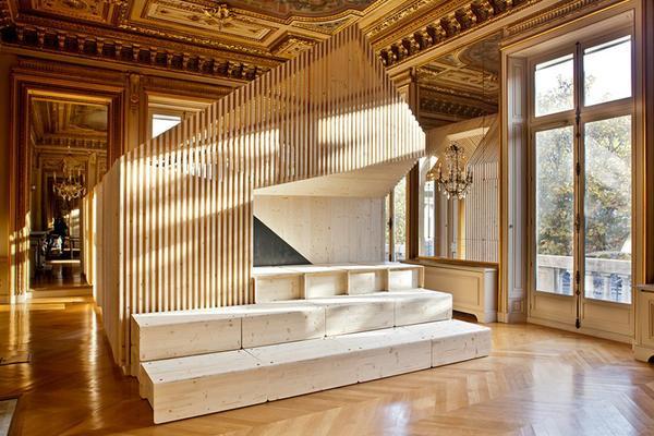 Văn phòng của công ty tư vấn marketing EKIMETRICS nằm trên đại lộ Champs-Élysées tại Paris có không gian rộng 10.700 m2. Nhưng chính vì nét quý tộc hoàng gia của không gian này mà việc thiết kế phòng họp lại là nhiệm vụ nhức đầu. Và cuối cùng căn phòng họp không gian mở với những bậc thềm lát gỗ như ngồi ngoài quảng trường này lại là nét hòa hợp giữa thiết kế hiện đại trong không khí cổ điển nơi đây.