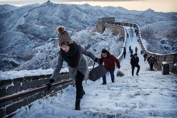 Dù mới đầu mùa nhưng tuyết đã rơi khá nặng tại Trung Quốc, bao phủ khắp nơi thành một lớp dày. Nhiều du khách tham quan Vạn Lý Trường Thành phải di chuyển từng bước đế tránh bị trượt ngã khi bước trên lớp băng trơn.