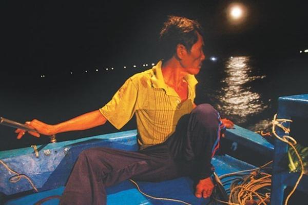 """Bằng cách lặn hàng giờ dưới biển, dùng thanh sắt sắc nhọn để xiên, cứ như vậy suốt đêm rồi trở về bờ vào mỗi buổi sáng. Anh tâm sự, """"Trước đây tôi đi biển cho các chủ tàu cá ra tận Trường Sa, sau tám năm chắt bóp tôi mua một chiếc thuyền nhỏ rồi tự ra biển đánh bắt cùng con trai. Do thuyền nhỏ không thể đi xa bờ nên đành chọn cách kiếm sống bằng nghề lặn đêm săn bắt cá"""". Trong ảnh: Ông Khiểm (50 tuổi), là người đảm nhiệm việc di chuyển thuyền theo ba người còn lại đang lặn bắt cá dưới đáy biển."""