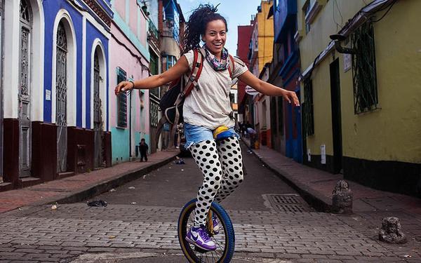 """""""Khi chụp ảnh phụ nữ, tôi nói chuyện với họ rất nhiều. Tôi cố gắng khiến cô ấy cảm thẩy mình đặc biệt, tự hào và duy nhất. Tôi có thể nói 5 ngoại ngữ và điều này giúp ích cho việc giao tiếp rất tốt. Nhưng ở nhiều nơi thì ngôn ngữ cơ thể lại thay thế tất cả"""". Đây là bức ảnh chụp cô gái đi xe một bánh tại Bogota, Colombia."""