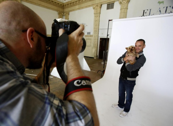"""In this photo taken on Saturday, Nov. 14, 2015, photographer Jesse Freidin shoots portraits of Dr. Robert Garofalo and his dog, Fred, in Chicago. Garofalo, who is head of the adolescent medicine division at Lurie Children's Hospital of Chicago, tested positive for the AIDS virus in 2010. He fell into a deep depression and credits Fred, a Yorkshire terrier, with bringing him back to life. Garofalo has since co-founded the """"When Dogs Heal"""" photo project, which features Freidin's portraits of HIV-positive people and their dogs. The exhibit opens in Chicago on Dec. 1, which is World AIDS Day, and in New York City on Dec. 3. (AP Photo/Martha Irvine)"""