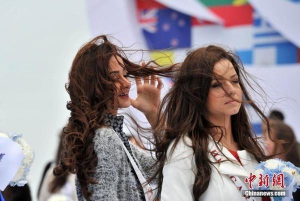 Các người đẹp phải đưa tay chỉnh tóc liên tục.