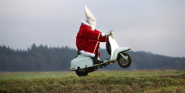 Một chàng trai trong trang phục Ông già Noel phóng vespa về nhà sau tiệc Giáng sinh gần Laubbach, Germany.