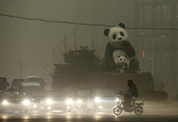 Một người dân lái xe đạp điện qua con phố dày đặc khói bụi tại Bắc Kinh, Trung Quốc. Tình trạng ô nhiễm không khí đang diễn ra ngày càng nghiêm trọng tại đây, mọi thứ đều chìm trong màn sương mờ mịt. Ảnh chụp ngày 1/12.